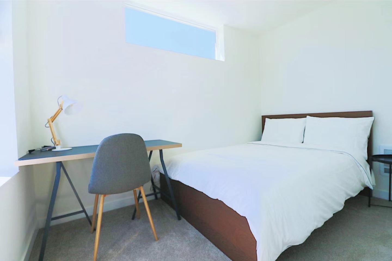 clean bedroom, wood study desk, white comforter