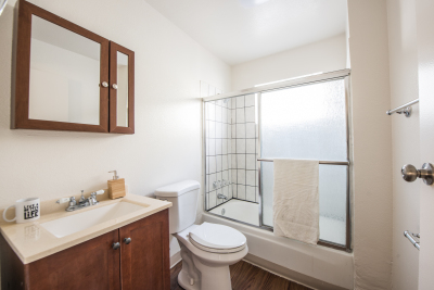 clean restroom with brown wood cabinet