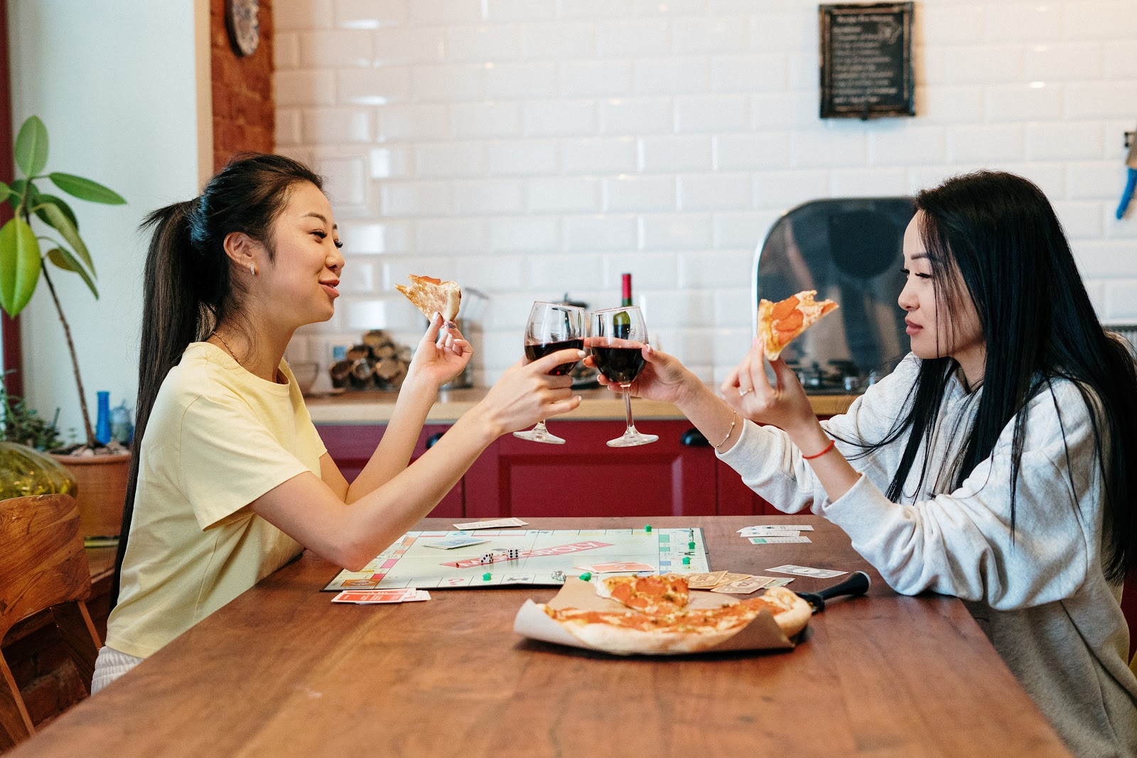 two women drinking wine and eating pizza