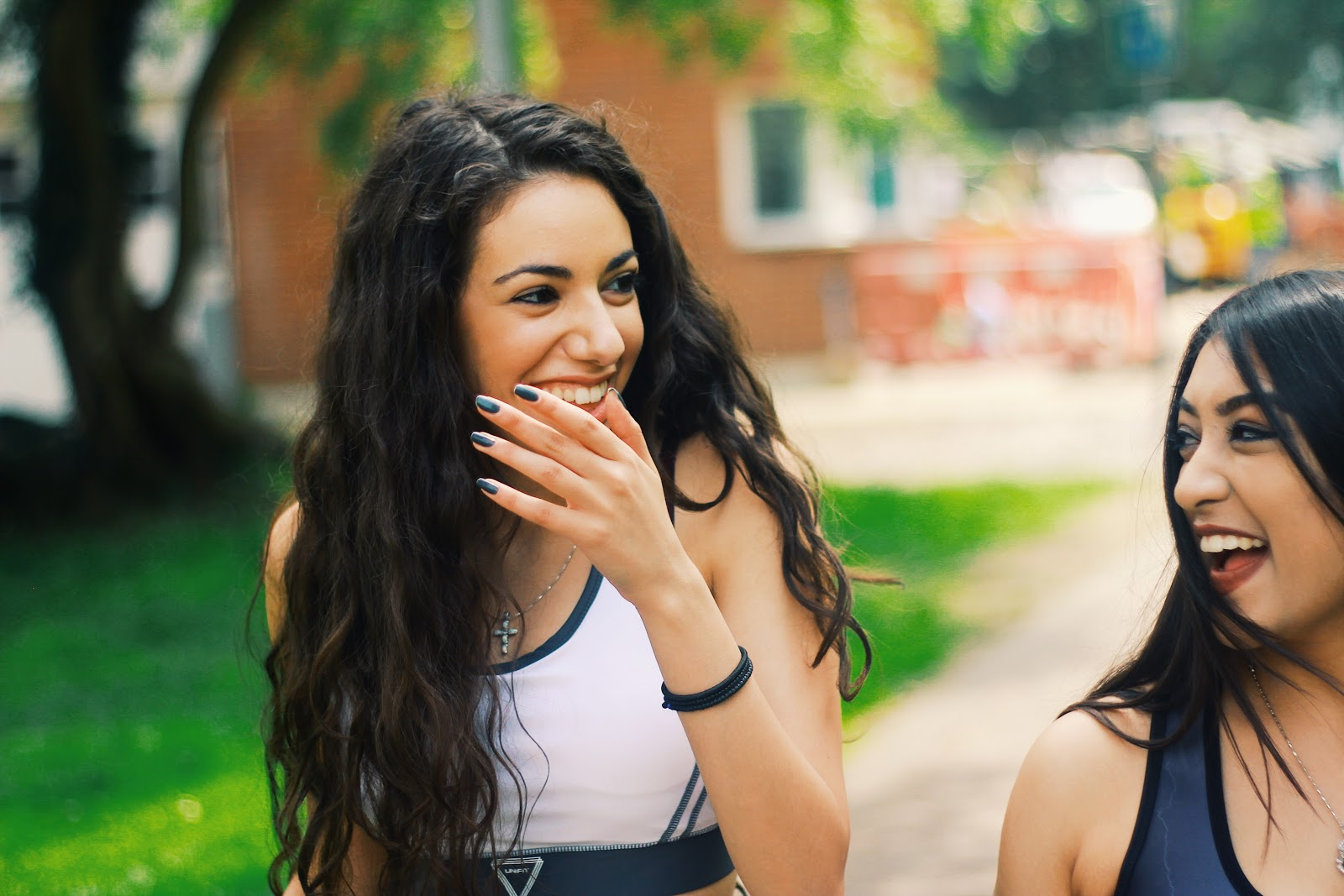 two girls laughing and smiling with each other on University campus