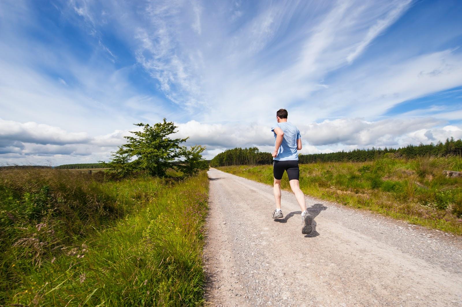 guy jogging down open trail