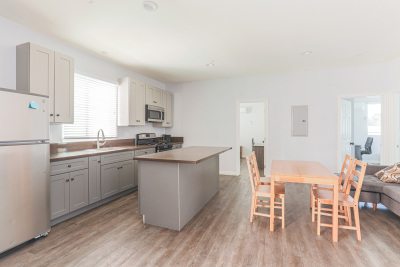 Side kitchen view, Brown wood dining table, granite kitchen isle
