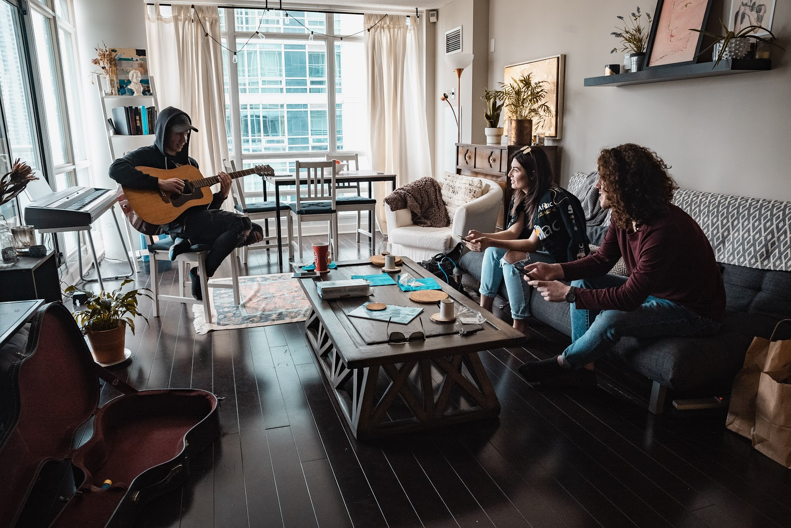 woman playing guitar for two women on a couch