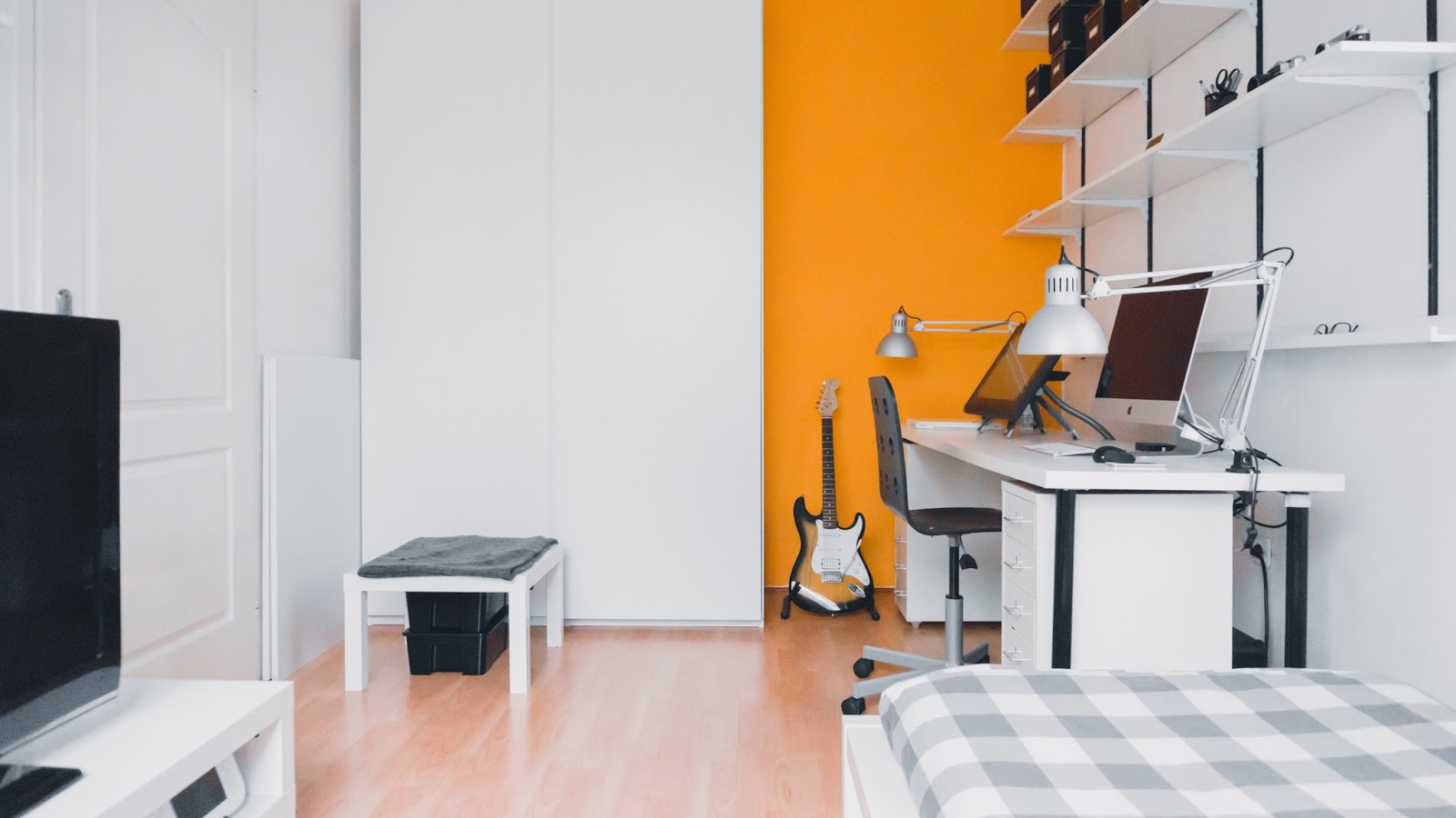 modern apartment bedroom with bright orange accent wall