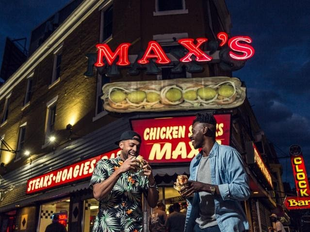 A couple of men standing in front of Max's Steak's