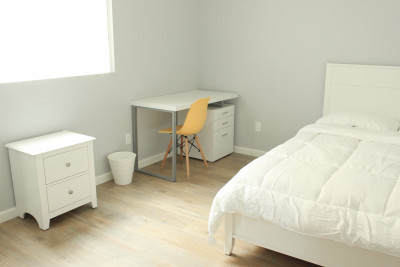 bright bedroom with cabinet, table and bed