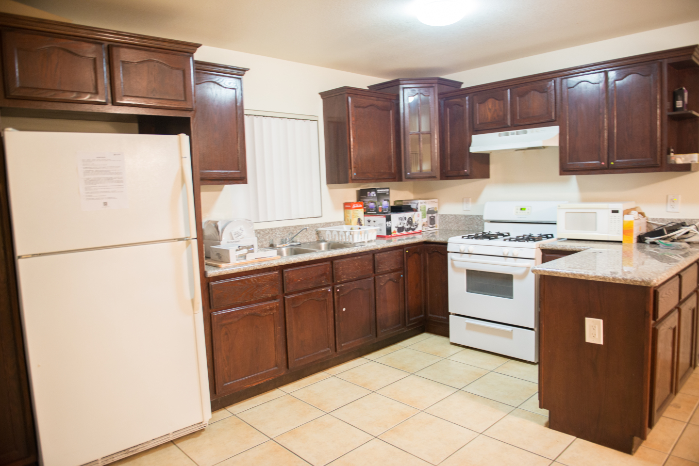 Large Kitchen, brown cabinets and white fridge