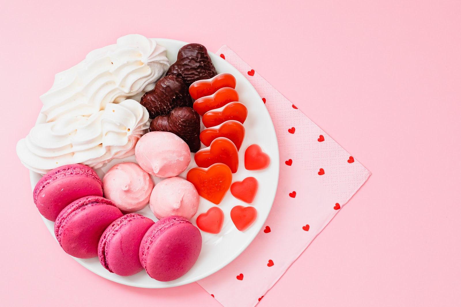 Valentines day desserts with pink macaroons and hearts